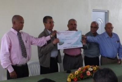 López entrega el cheque a respresentantes de la cooperativa LV.