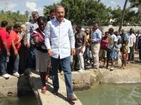 El presidente Danilo Medina cruza un puente ir a observar las jaulas de cultivo de peces del Proyecto Centro de Producción Piscícola de La Bombita.